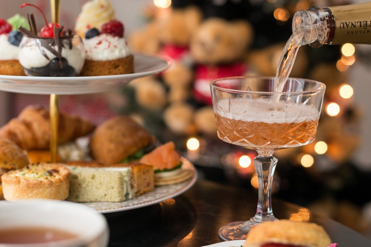 Glass of Champagne being poured with cake stand featuring sweet and savoury treats