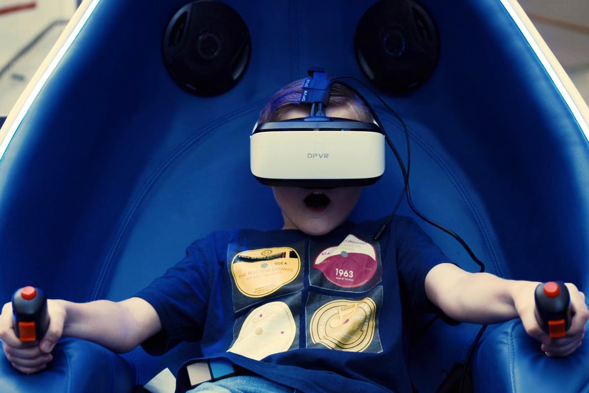 Boy with VR technology headset in an individual pod with surround sound