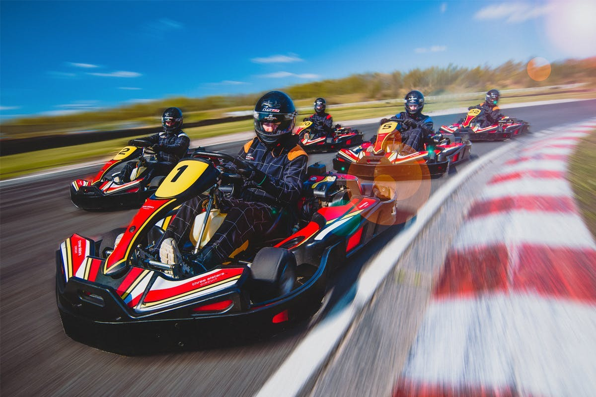 Karts racing around a track with blue sky