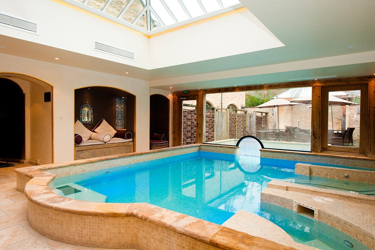 Indoor pool with seating area and terrace outside