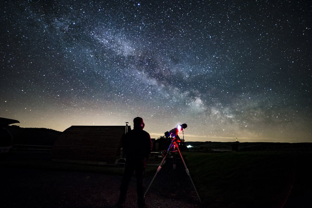Man on his own with telescope overlooking starry sky