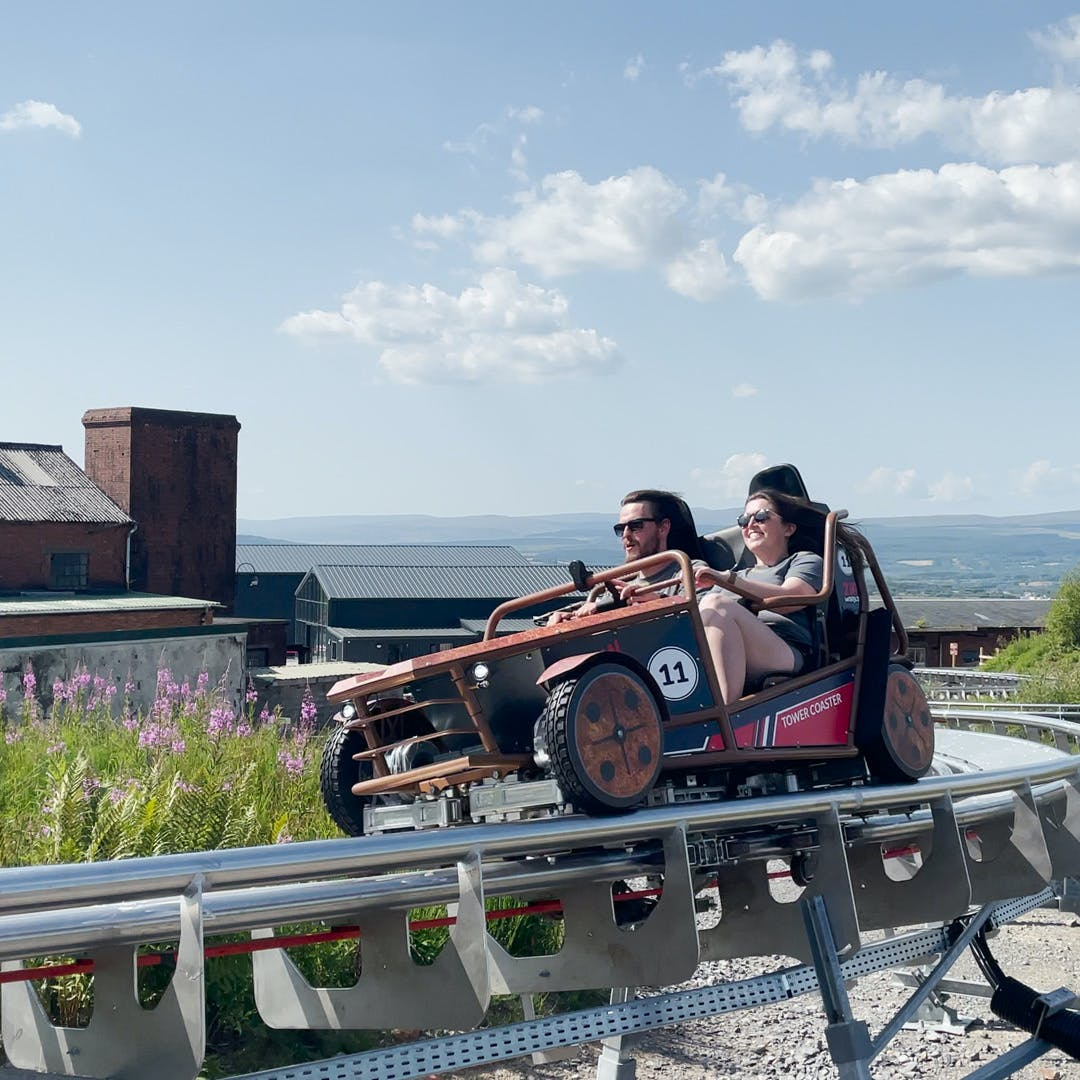 Two people sat next to each other racing around the track on rollercoaster
