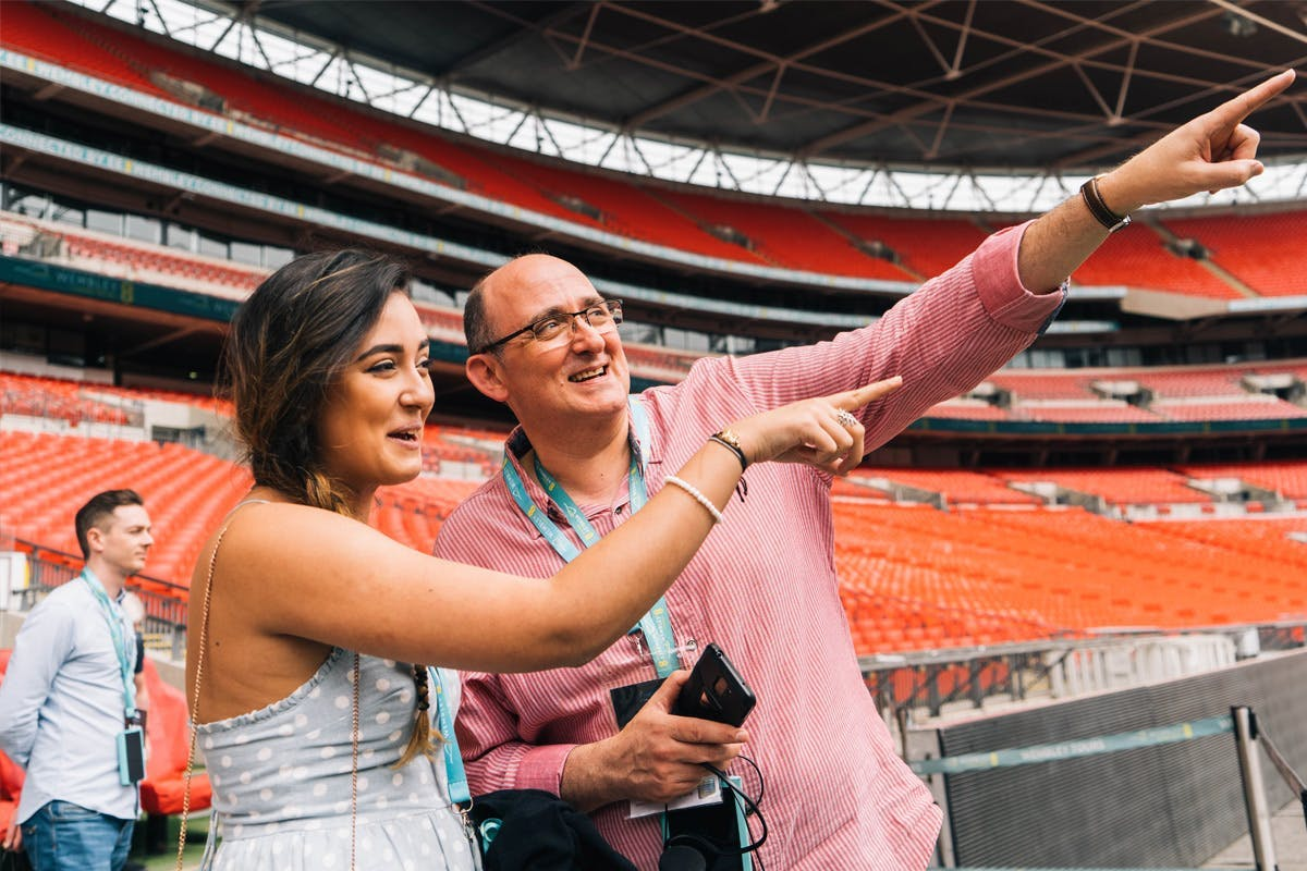 Wembley stadium tour showing two people pointing across the stadium